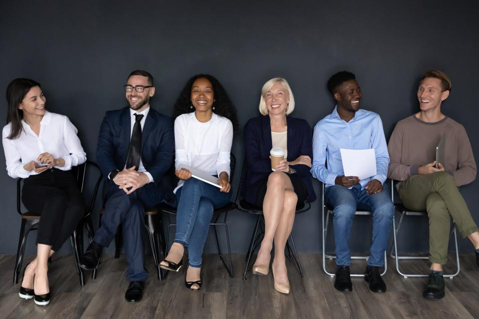 Happy multiracial businesspeople group sit on chairs laughing, human resource