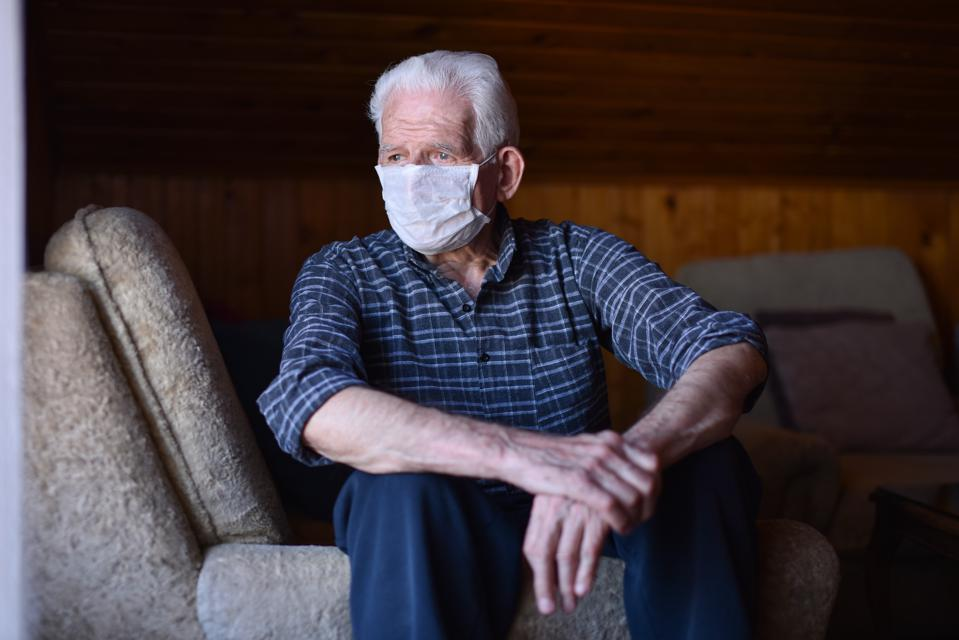 Portrait of senior man with respiratory mask looking outside from home window during quarantine