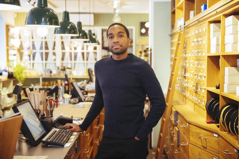 Portrait of confident young male owner standing at checkout counter in furniture store