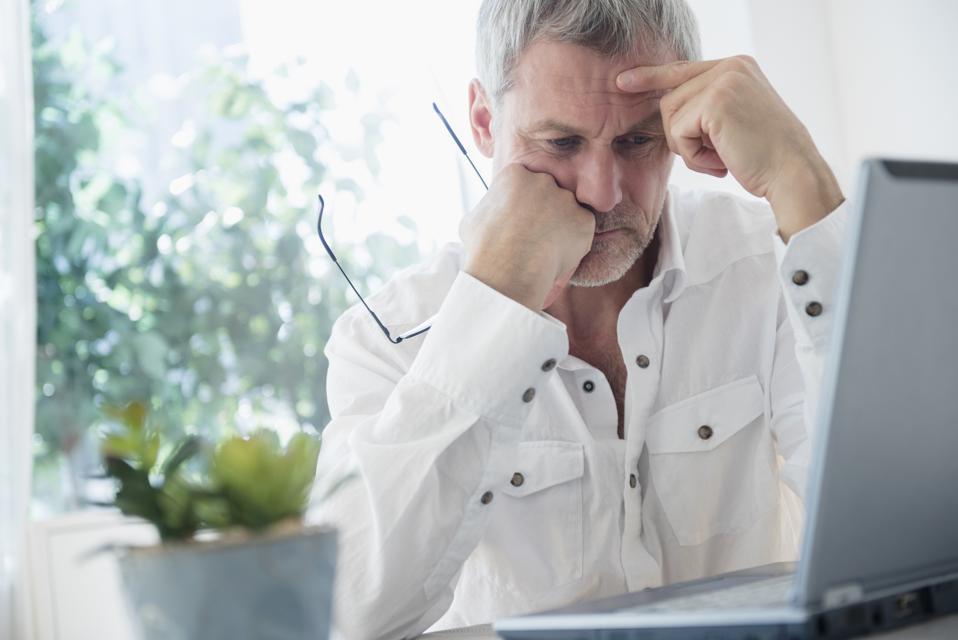 Frustrated older Caucasian man using laptop