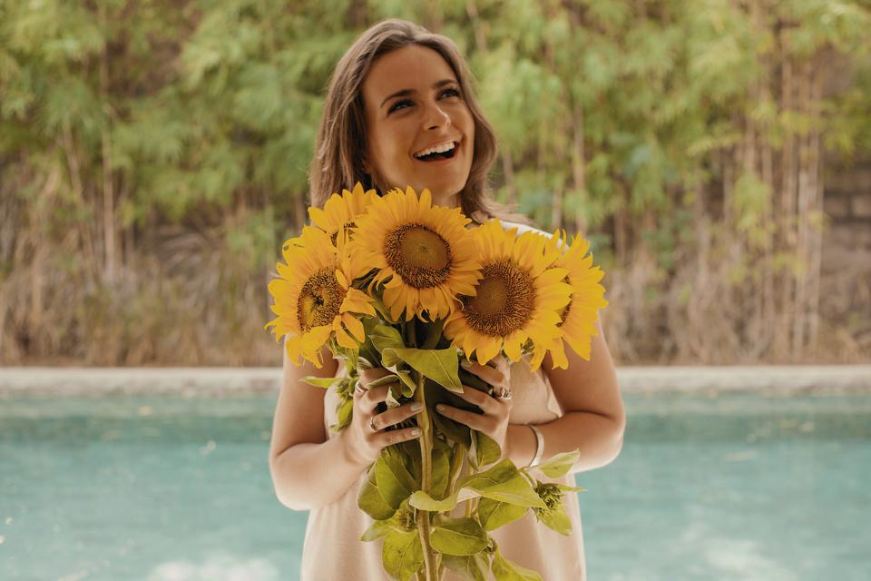 attractive woman holding sunflowers and laughing, brand story coach, mindset, storytelling strategist