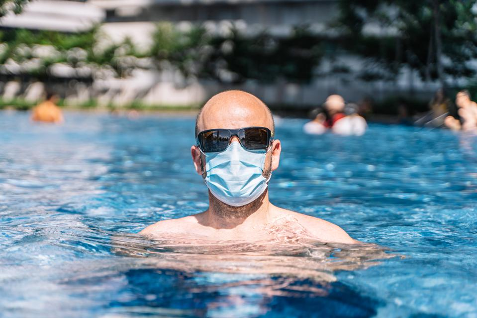 portrait of a tourist couple wearing a protective mask inside the pool for fear of the coronavirus covid19