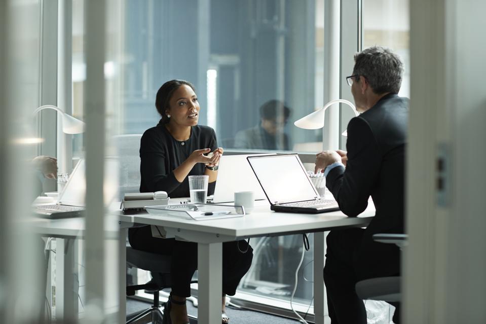 Businesswoman speaking with co-worker in open office