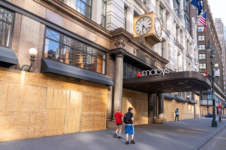 People walk by a boarded up Macy's flagship store in Herald...