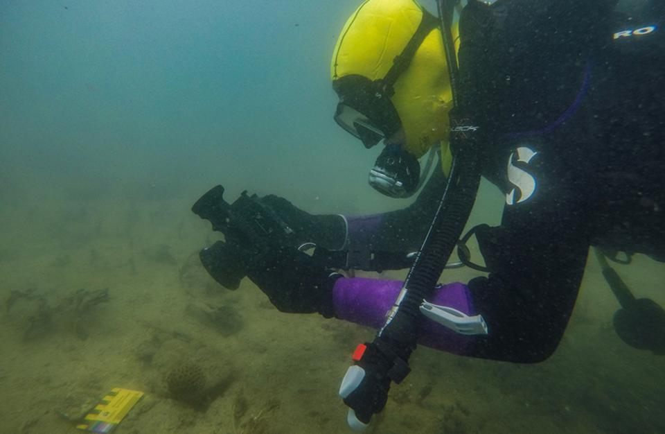 A diver underwater photographs a stone artifact found on the sea floor.