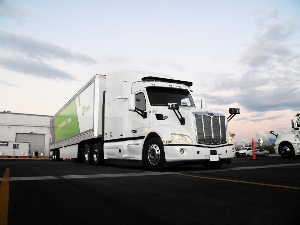 A TuSimple autonomous freight truck at a delivery depot.