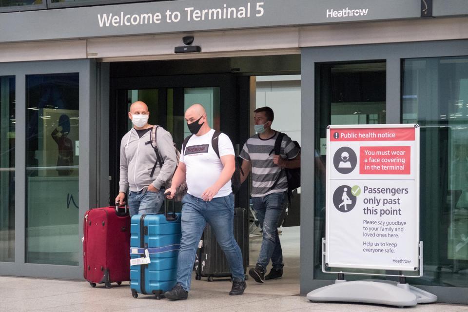Travelers arrive at Heathrow airport London UK