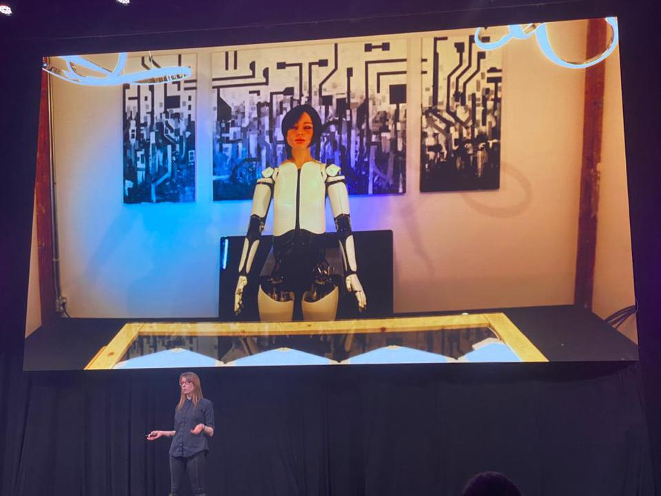 Woman speaks on stage about robots.