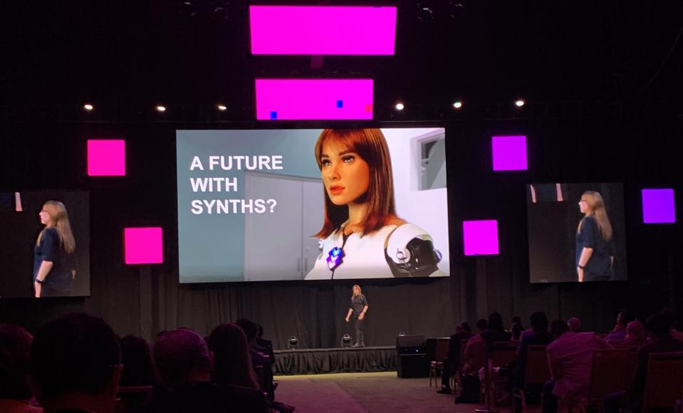 Woman on stage talks about robots.