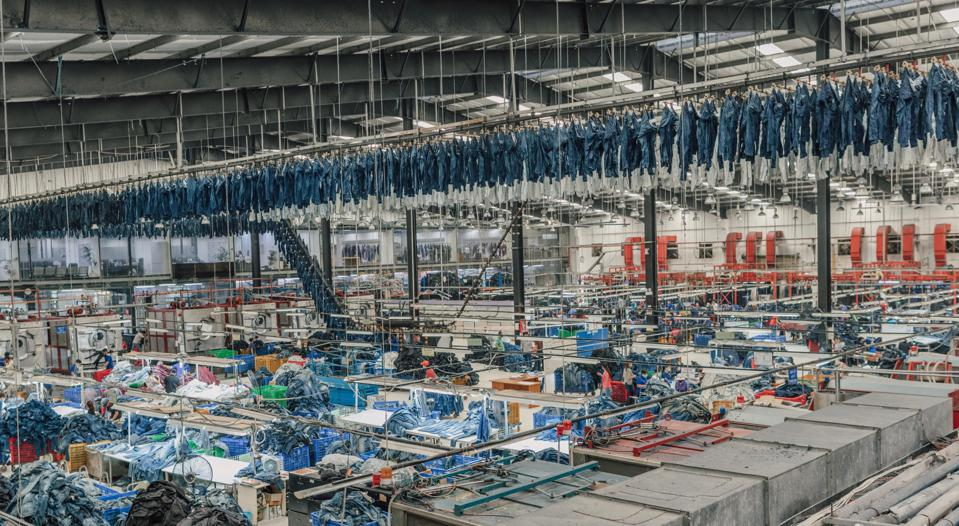 denim factory with mass produced jeans hanging above sewing machines