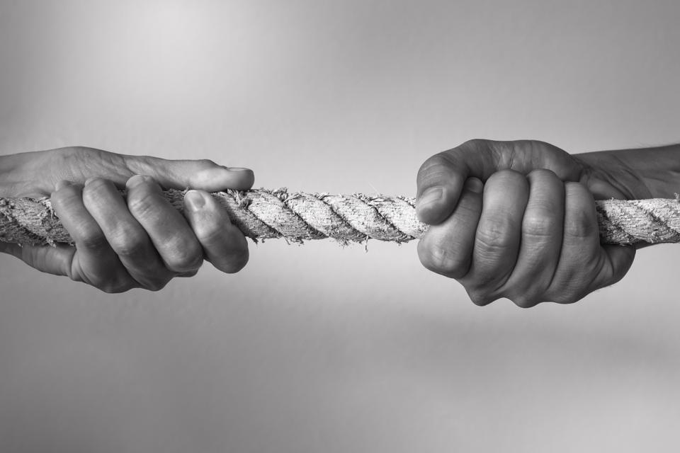 Hands pulling rope playing tug of war.