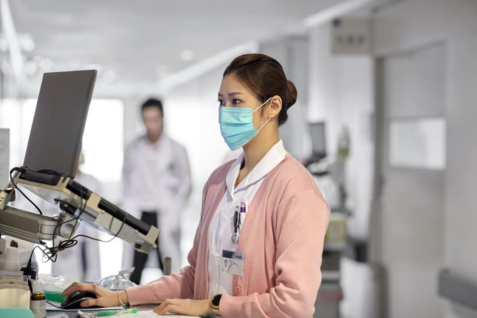 Female Nurse using laptop in hospital