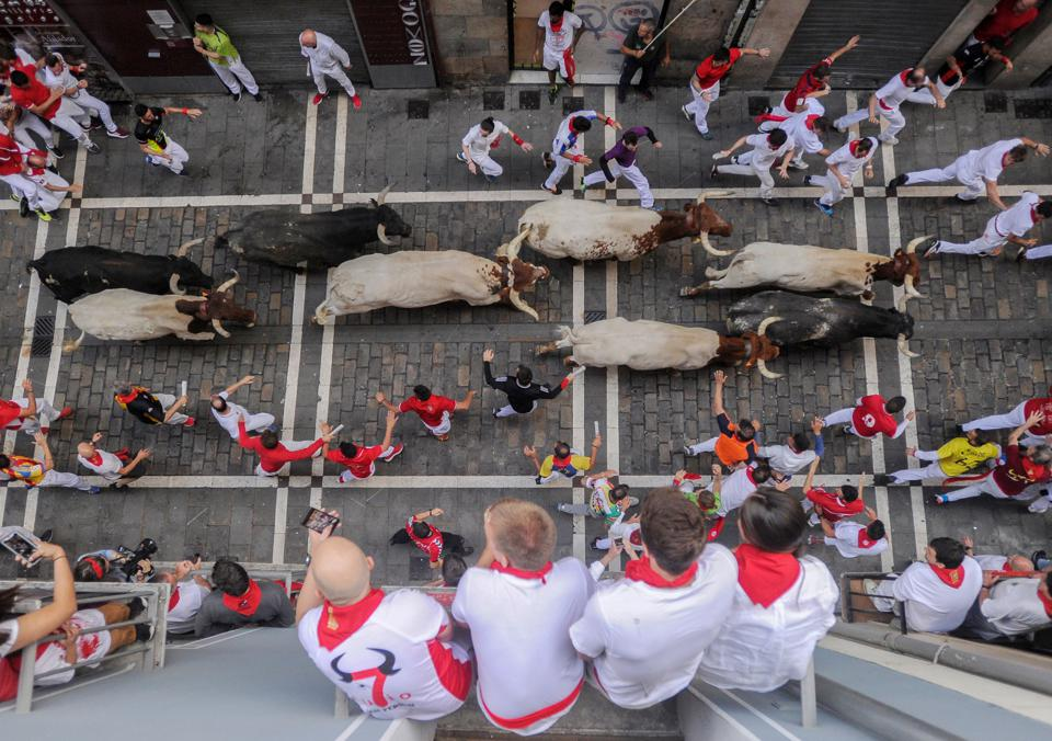 Revellers observe participants run with bulls at the San Fermin festival in Pamplona, northern Spain, on July 12, 2019.