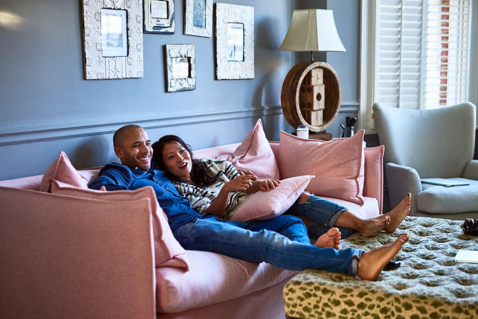 Couple at home watching television together on sofa