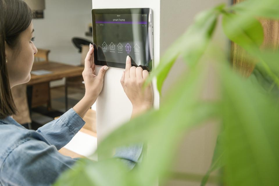 Young woman with tablet with smart home control functions