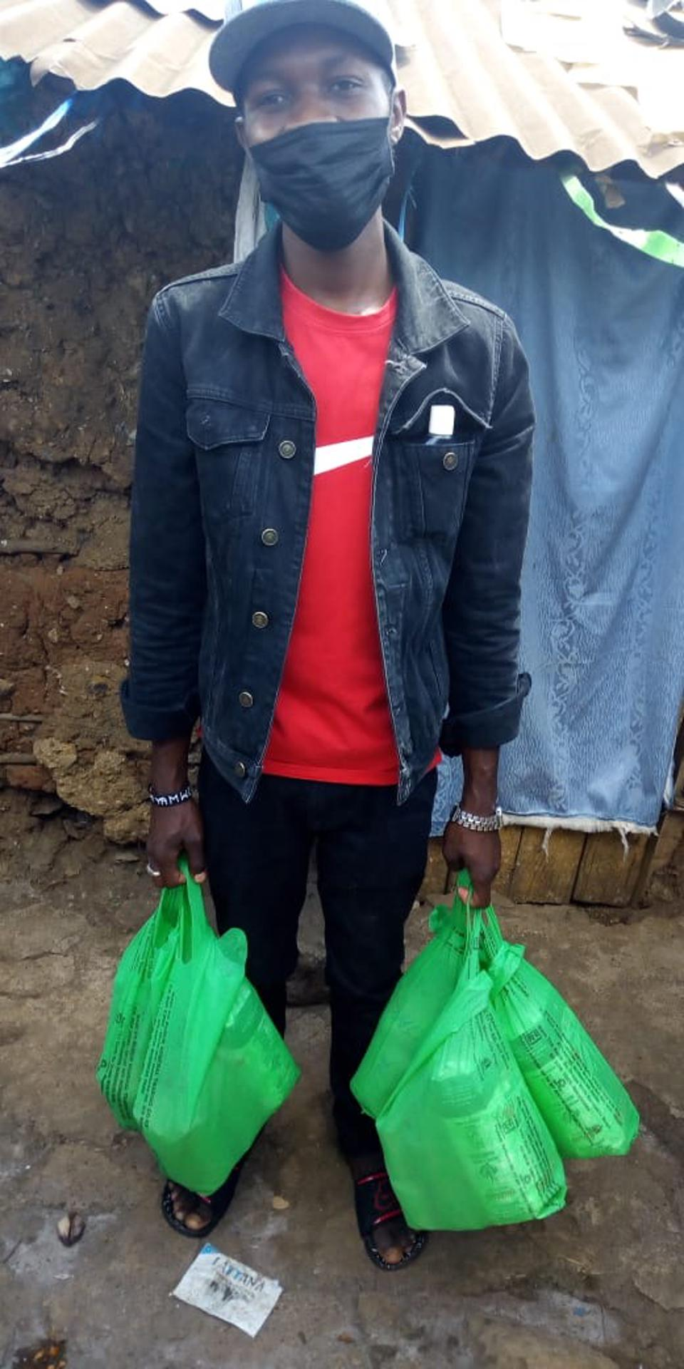 Man in jacket and red shirt holding green bags.