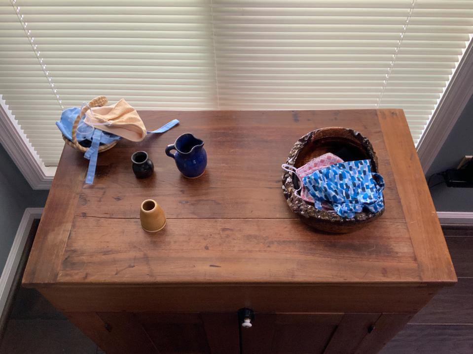 Mask basket on table near entry.