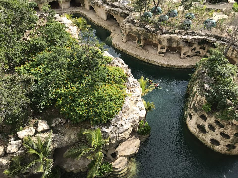 Overhead view of a kayak in a cenote river surrounded by platnts and stone islands, at Hotel Xcaret Mexico