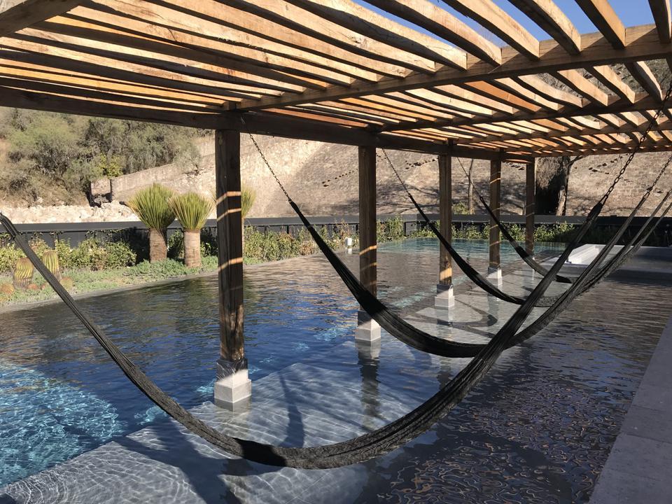 Hammocks near part of the pool at Live Aqua Urban Resort San Miguel de Allende.
