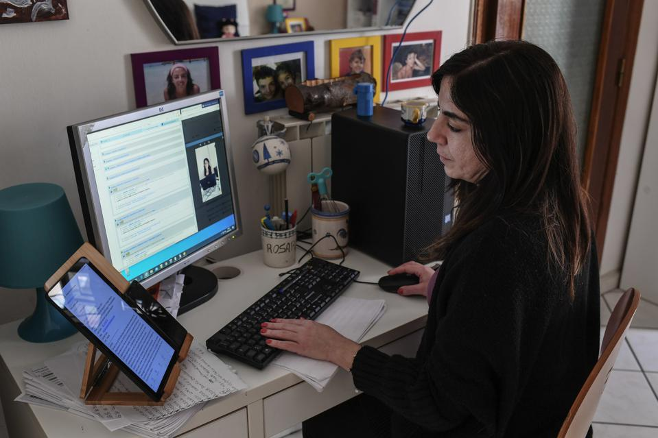 A woman works from her home in streaming contact with a colleague.