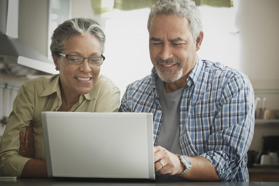 Hispanic couple using laptop in kitchen