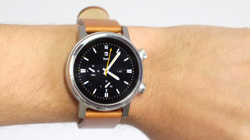 The Moto 360 worn on the wrist with its leather strap.