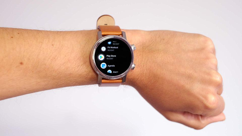The Moto 360, worn on a wrist, showing its app page.