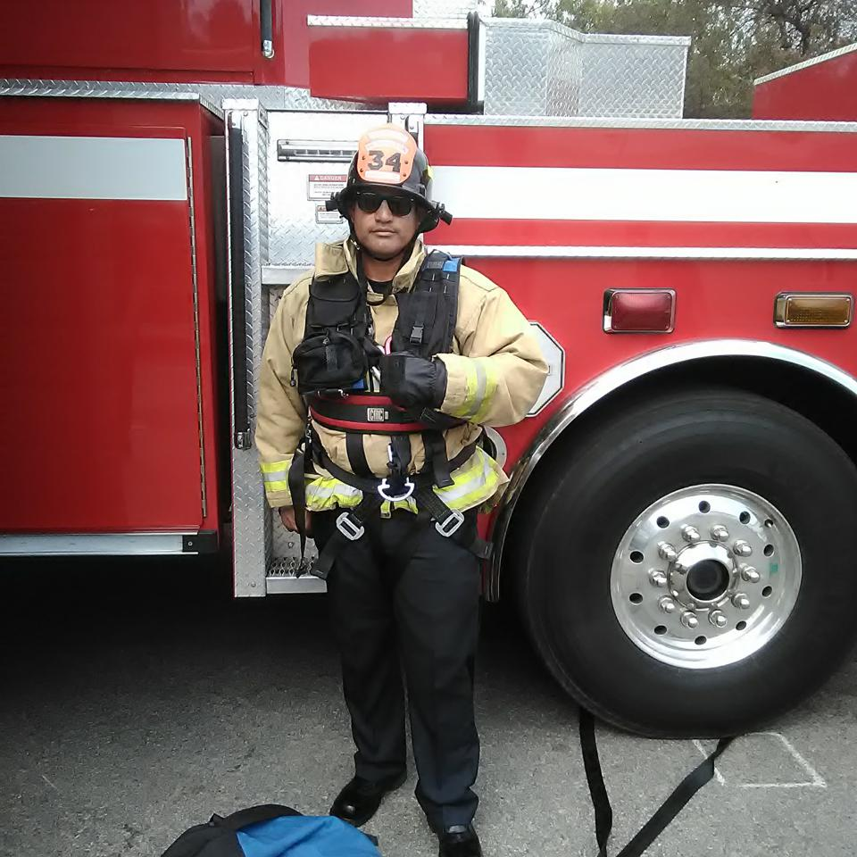 firefighter stands in front of fire truck