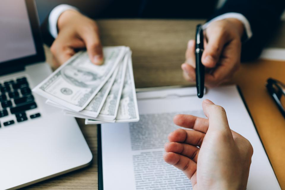 Partner has made a fraud in the contract of sale and being handed a cash and pen to the businessman signing the contract corruption bribery concept.