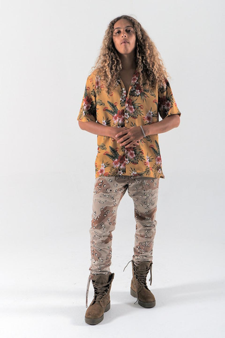 """Model Olan Prenatt wears a print was designed after reading about the history of the Aloha shirt and it's popularization on the """"mainland"""" after WWII.   The Tropical flowers are the main focal point but scattered throughout are lipstick motifs representing the kisses Women placed on letters that they sent to their men stationed in the Pacific.  It is cut from 100% rayon and sewn in Los Angeles in a small family owned specialized shirting factory"""