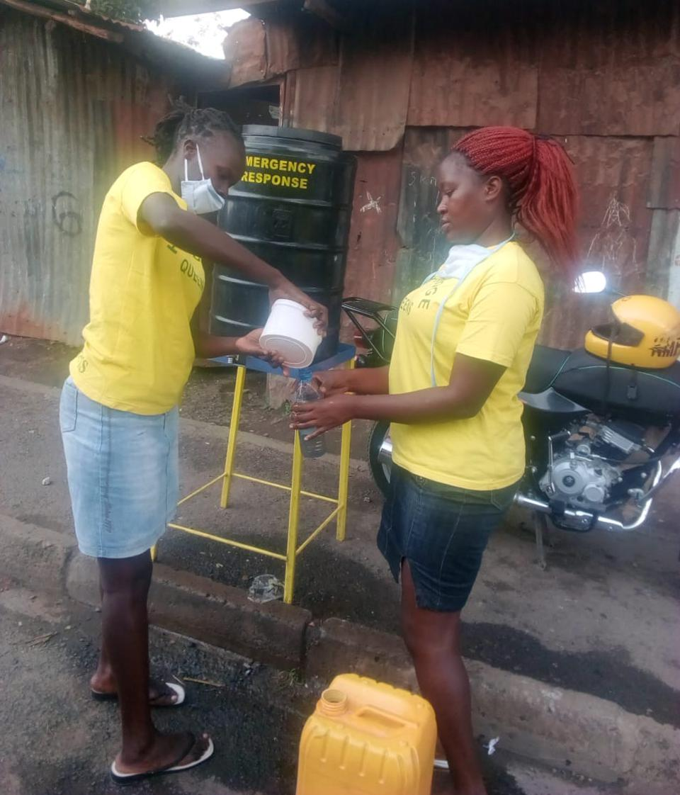 Two women in yellow shirts pouring out of a container