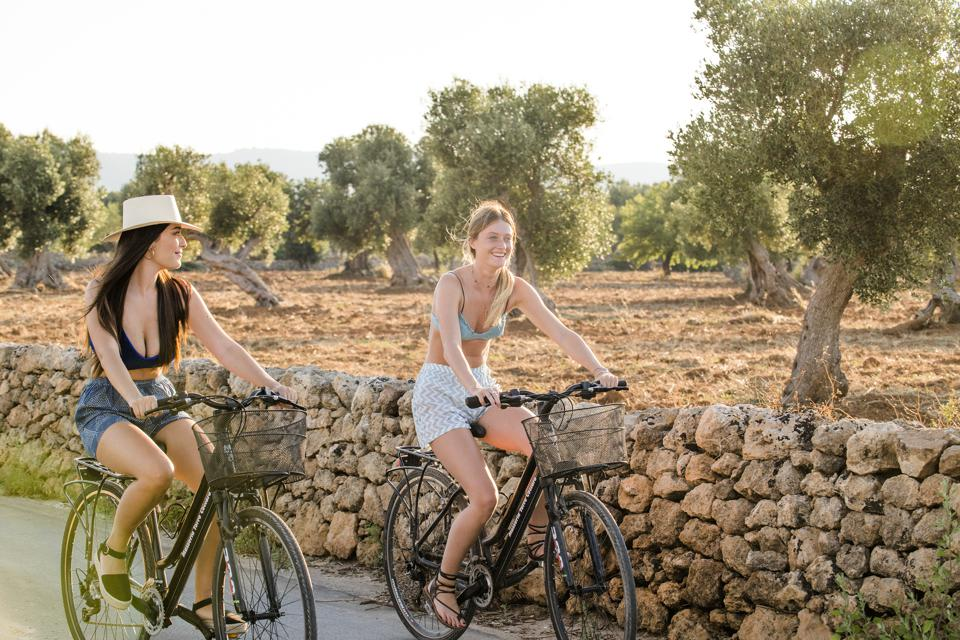 two girls ride bikes through Puglia olive groves southern Italy
