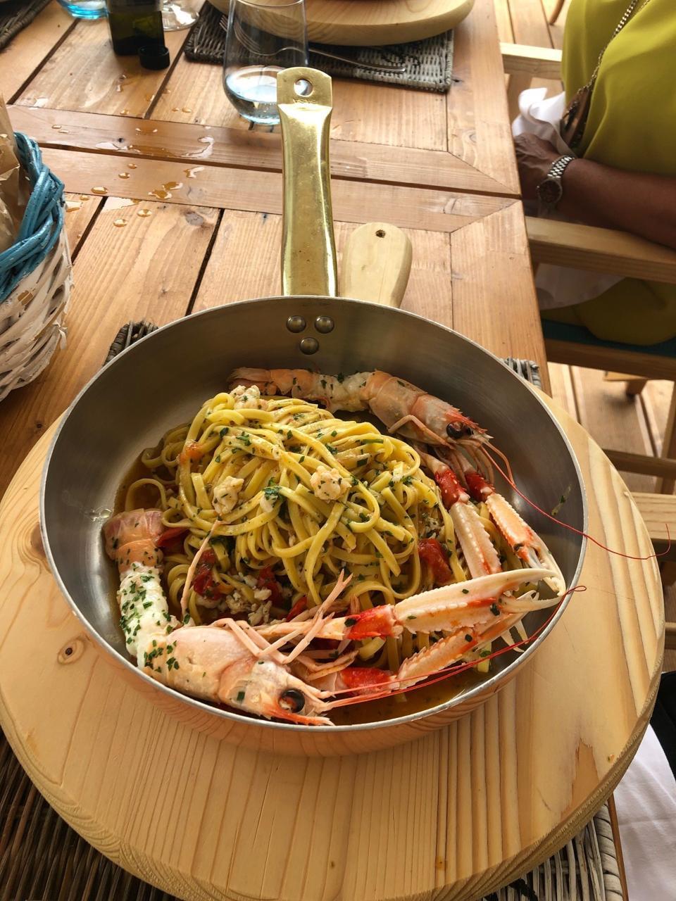 A restaurant skillet with Puglia linguine agli scampi linguine pasta with king prawns