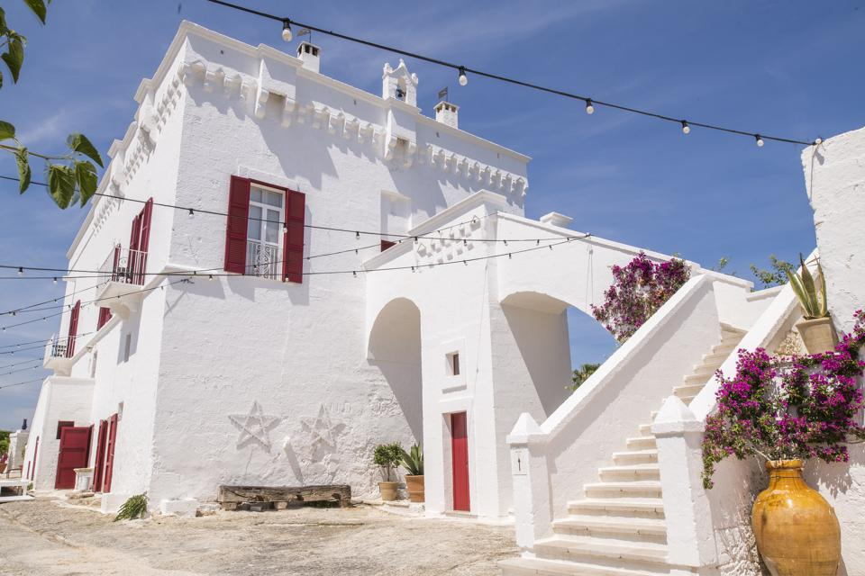 White washed Puglia masseria farmhouse luxury hotel with flowers and under blue sky