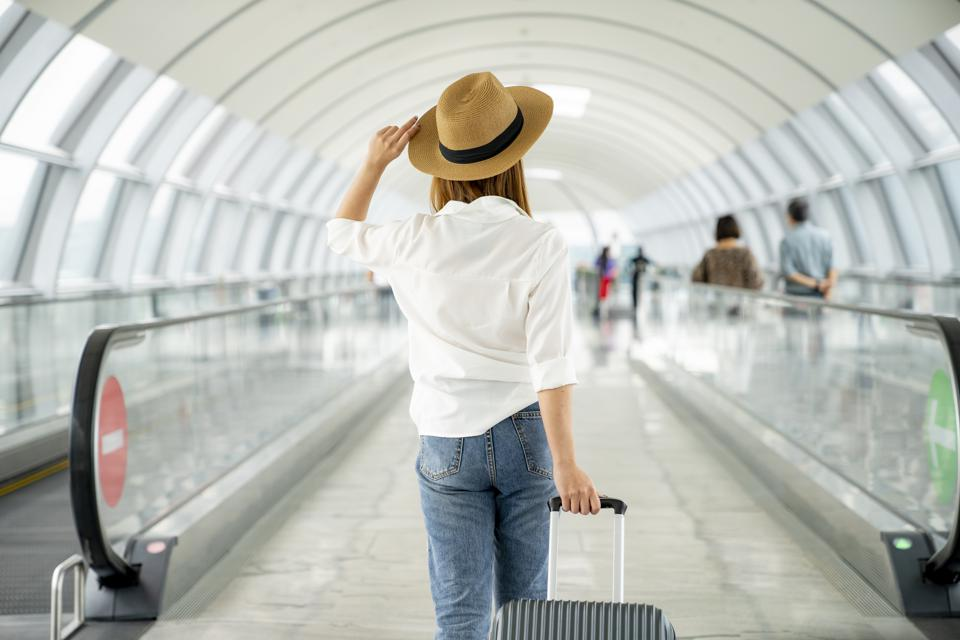 Young casual female traveler with suitcase at airport