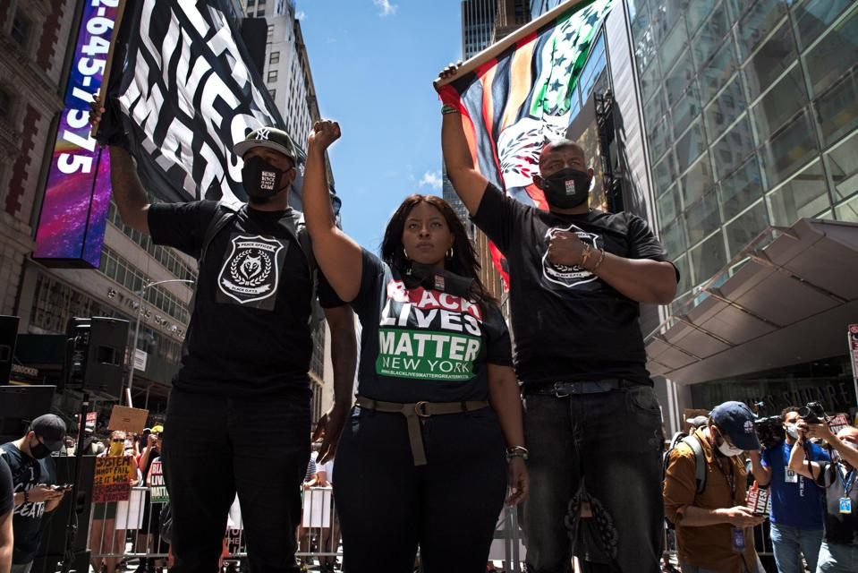Chivona Newsome (middle) and Hawk Newsome (right) protesting in Times Square.
