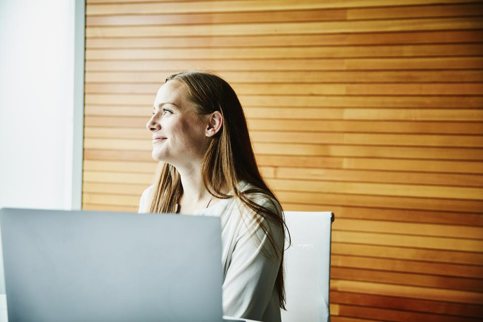 Portrait of smiling businesswoman working on laptop during meeting in office