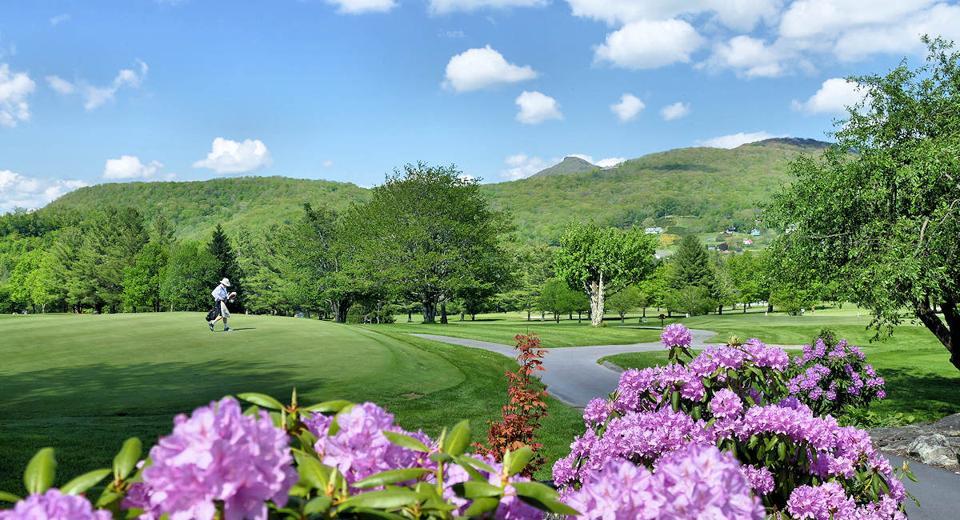 A lone golfer walks off the green at Sugar Mountain Golf Club.