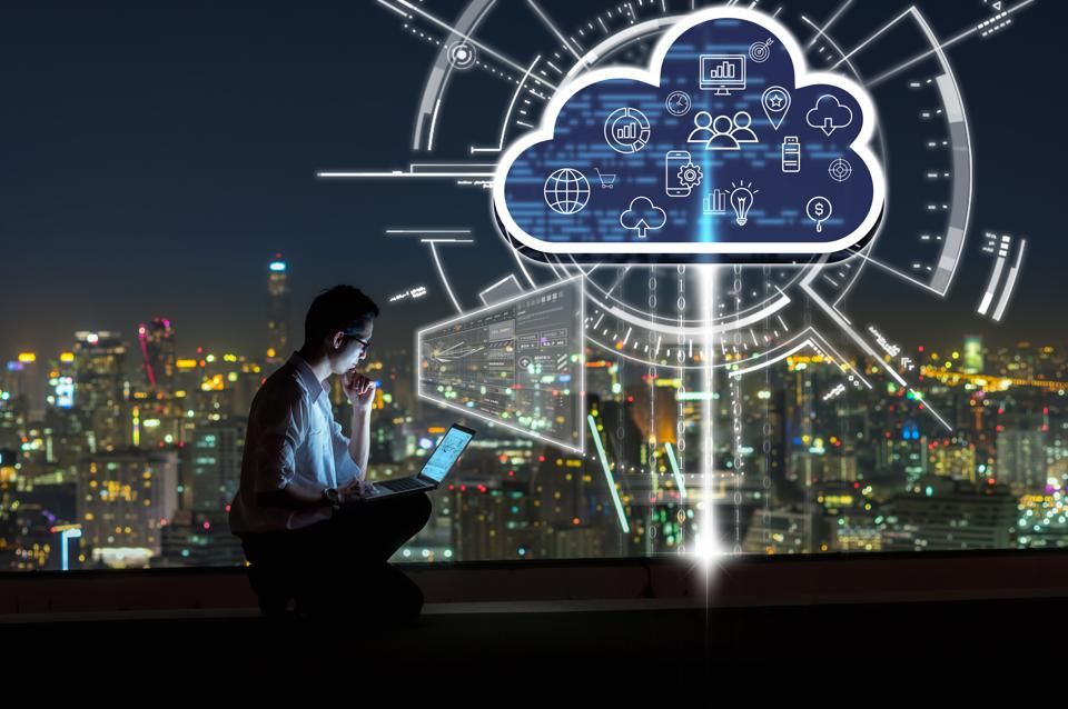 Business success and technology concept, Asian businessman sitting and using the laptop and working with virtual screen connecting with cloud technology over the cityscape background at night time