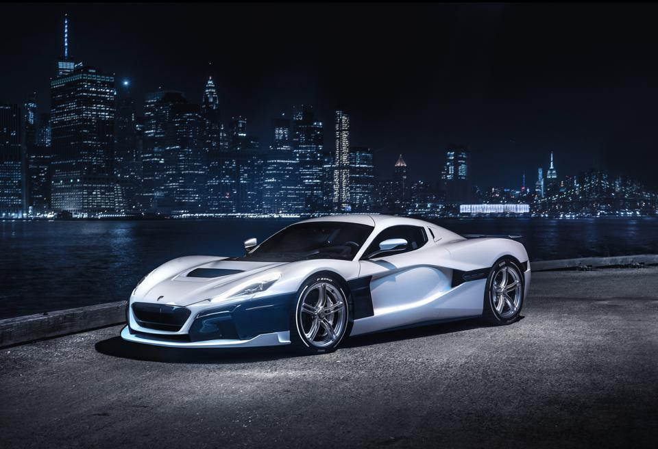 Rimac C_Two electric hypercar concept, in silver, in front of the New York skyline.