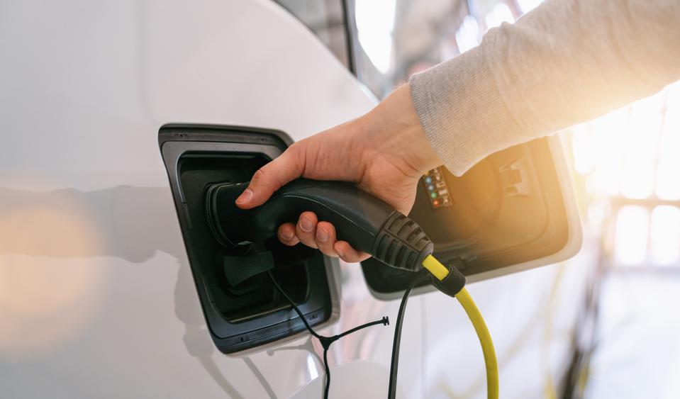 Hand holding Electric car charger. Power supply electric car charging for electric car technology transportation in the future.