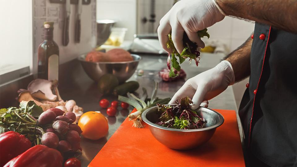 Gloved hands toss a salad in a professional kitchen.