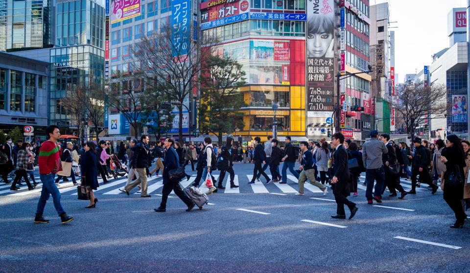 Crowds of pedestrians walking across a street in a Tokyo business district