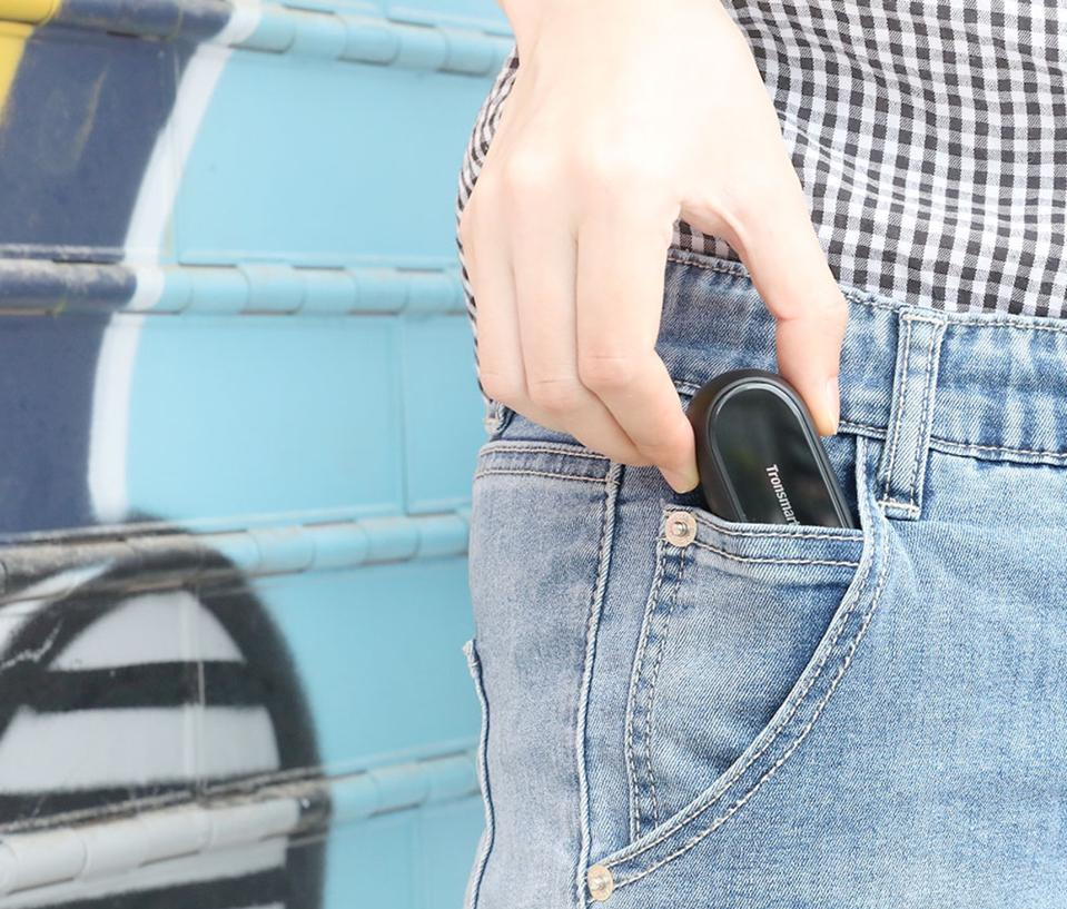 A person putting the Tronsmart Onyx Free charging case into a jeans pocket