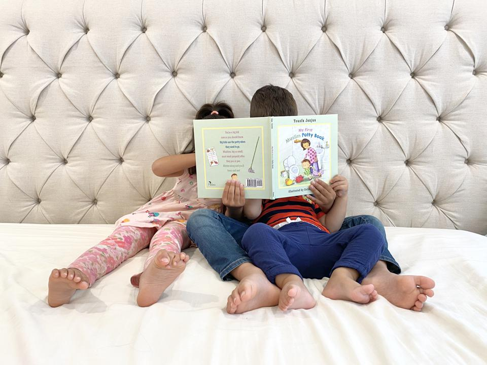 Three children read My First Muslim Potty Book.