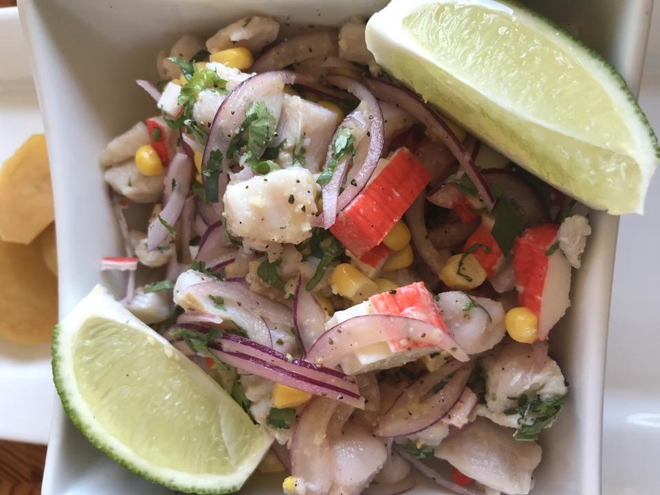 A bowl of ceviche, raw fish with onion, corn and herbs, served with lime slices