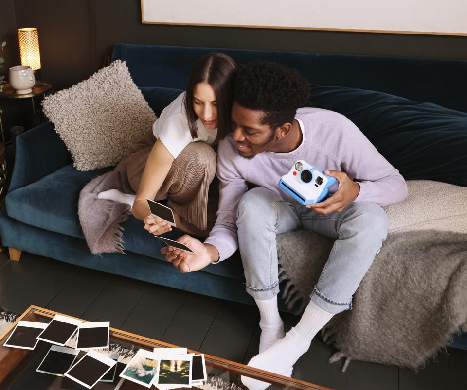 couple with polaroid now camera and photographs on couch
