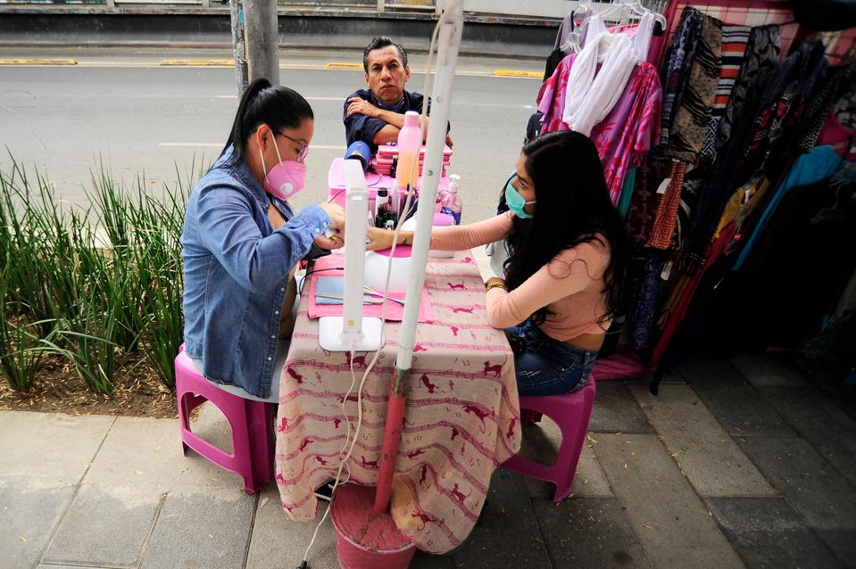 Mexico City, Mexico: A woman wears protective mask to prevent coronavirus disease while does a woman's manicure during the begin of phase 3 of COVID-19 on April 29, 2020 in Mexico City, Mexico.
