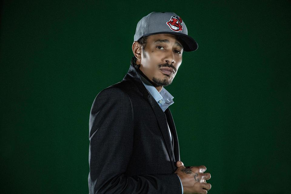 A man with a mustache in a blazer and ball cap against a green background.