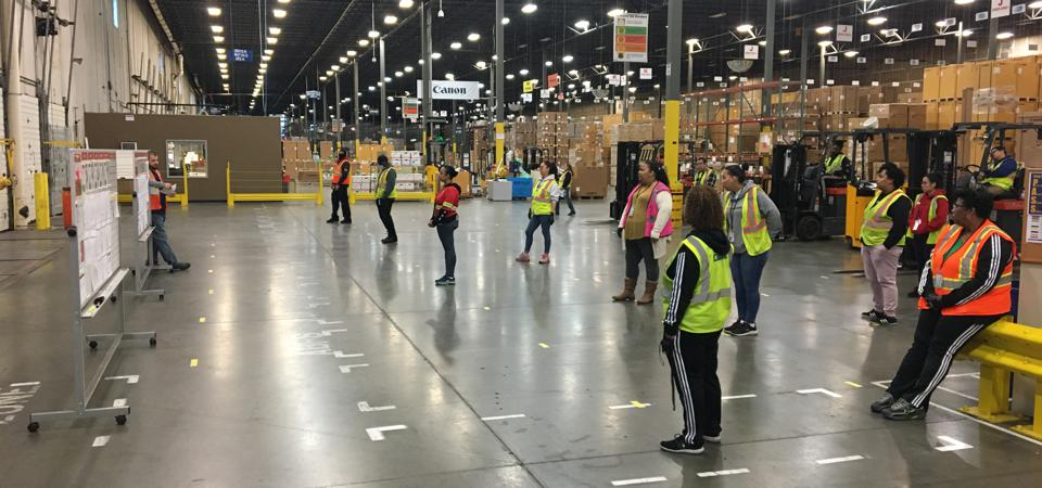 Warehouse workers gather for a pre-shift meeting.